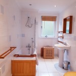 Spacious family bathroom with bath with shower over, toilet and wash hand basin